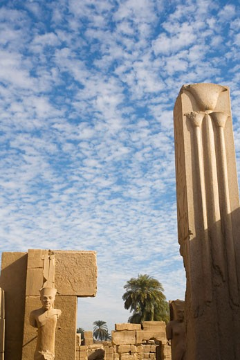 Stock Photo: 1909-3356 Granite pillar with papyrus decoration and statue in Temple of Amun Re Karnak Egypt North Africa Karnak Temple is the largest temple complex ever built and was gradually enlarged by successive pharoahs over a thirteen hundred year period