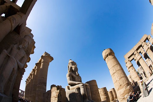 Statue of Ramses II in summer sun sunshine Karnak Temple Luxor Egypt Africa Karnak Temple is the largest temple complex ever built and was gradually enlarged by successive pharoahs over a thirteen hundred year period : Stock Photo
