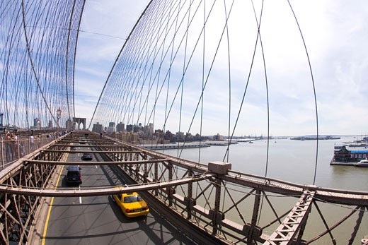 Stock Photo: 1909-3885 Brooklyn Bridge in spring sun sunshine with yellow taxi cab on road Lower Manhattan New York City NYC USA United States of America North