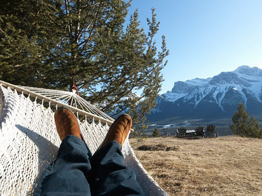 Detail of mans legs while lying in hammock  alpine meadow and Three Sisters Mountain behind  above Canmore  Canada  Alberta : Stock Photo