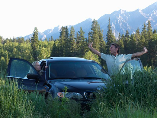 Couple stretch outside of car  parked in alpine meadow  Quarry lake  Canmore  Canada  Alberta : Stock Photo