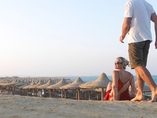 Man joins woman on sandy pow above beach palapas  Sahara Desert and Red Sea in distance  Egypt  Red Sea Riviera  Marsa Alam : Stock Photo