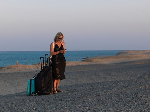 Woman 40s dials mobile phone while standing with luggage  in Sahara Desert  Red Sea below  Egypt  Red Sea Riviera  Marsa Alam : Stock Photo