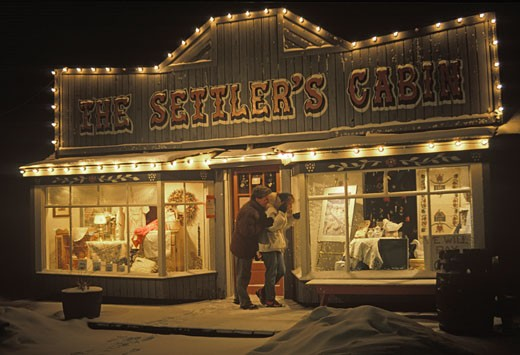 Stock Photo: 1910-1365 Couple outside Settlers Cabinstore in Canmore during winter evening CANADA Alberta