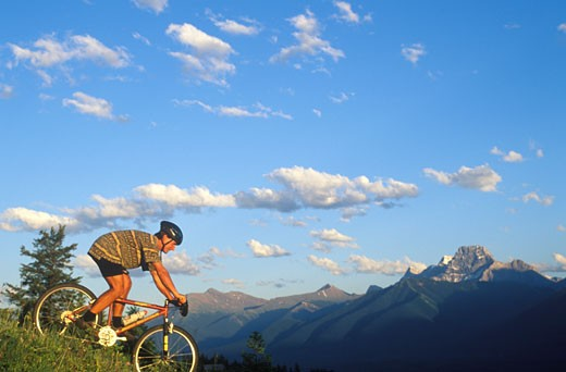 Mountain biker descending steep slope Mt Lougheed in distance above Canmore CANADA Alberta : Stock Photo