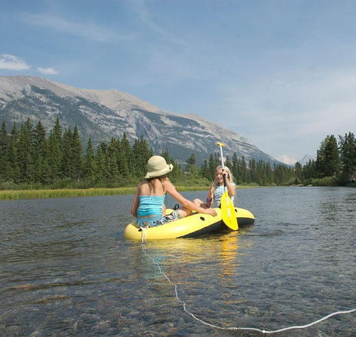 Girls 10-11 yrs drifting down creek in inflatable raft Canmore CANADA Alberta : Stock Photo