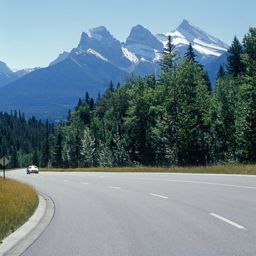 Road with single car and Three Sisters Mountain Canmore CANADA Alberta : Stock Photo