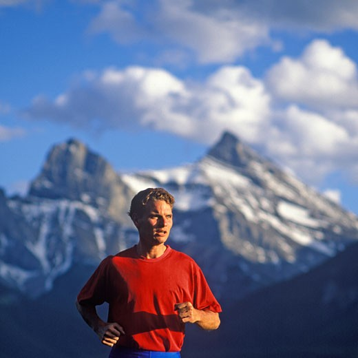 Stock Photo: 1910-1383 Man 30 yrs running up mountain slope Three Sisters Mountain behind Canmore CANADA Alberta