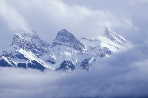 Three Sisters Mountain with snow and morning clouds rising above Canmore CANADA Alberta : Stock Photo