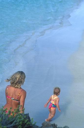 Stock Photo: 1910-1491 Mother and child 2 years walking along edge of beach viewed from high perspective Varadero beachsome call it the worlds greatest beachhas long been the pride of Cuba and a magnet for the rich and famous CUBA Varadero