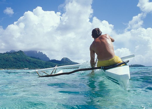 Man paddling outrigger canoe towards distant mountains through gentle waves and clear waters Outrigger canoes are native to the Polynesian islands where they have been used for centuries TAHITI French Polynesia Bora Bora : Stock Photo