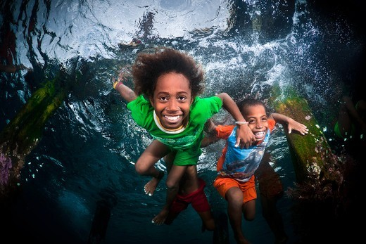Indonesia, North Raja Ampat, Local  kids swimming in sea : Stock Photo