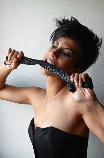 Stock Photo: 1916-7673 Wild attractive short haired woman bites  belt