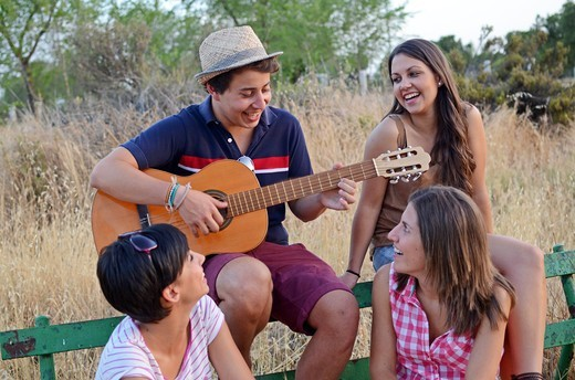 Young man plays Spanish guitar for her three friends : Stock Photo