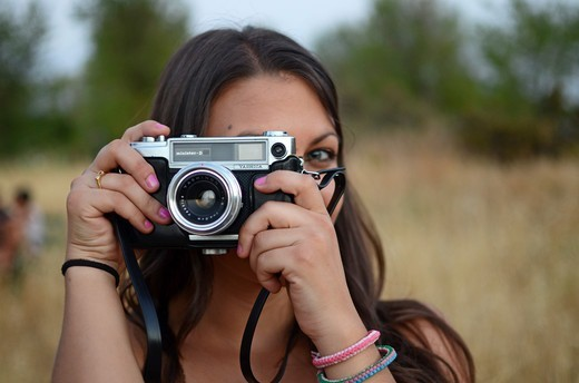 Stock Photo: 1916-7699 Cute young woman using  old camera