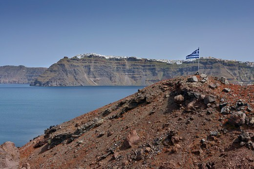 Stock Photo: 1916-7882 Small hill with the Greek flag and Fira in the background, Nea Kameni, Santorini, Greece