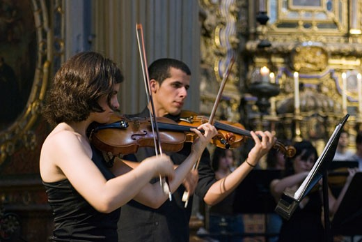 Young violinists playing in San Luis de los Franceses church  Seville  Spain : Stock Photo