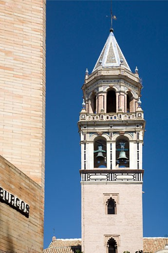The bell tower of San Pedro church in front of a modern building wall  Seville  Spain : Stock Photo