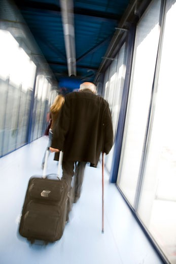 Old man drawing a roller suitcase through an airport corridor : Stock Photo