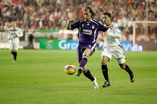 Stock Photo: 1925-1469 Sergio Ramos pursued by Adriano Taken at Sanchez Pizjuan stadium Seville  Spain on 9 December 2007 during the Liga game between Sevilla FC and Real Madrid The final score was 2 1 for Sevilla  the home team
