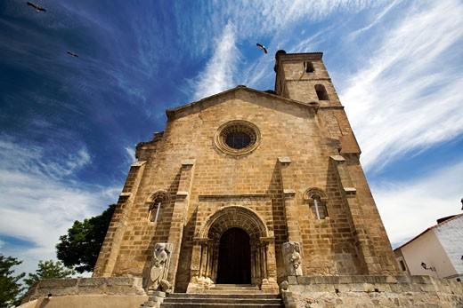 Storks flying over the Romanesque church of Santa Maria de Almocovar  built over a former mosque  Alcantara  Caceres  Spain : Stock Photo