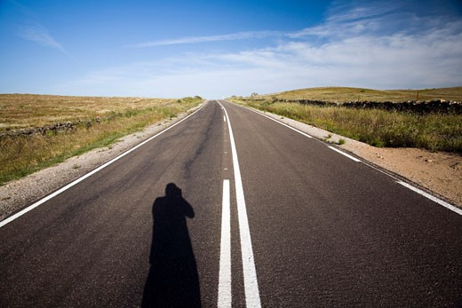The shadow of a man on a lonesome road  province of Caceres  autonomous community of Extremadura  Spain : Stock Photo