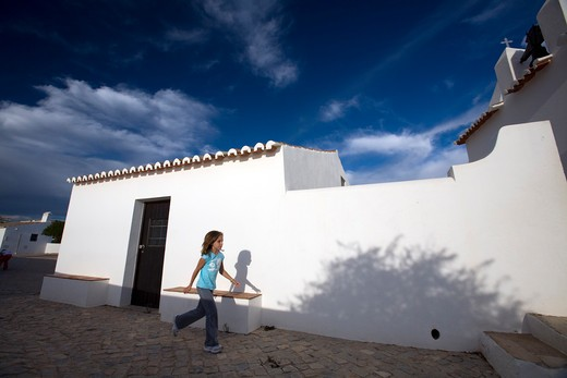 Stock Photo: 1925-2133 Girl walking in front of a typical architecture building, Porches, Lagoa, Faro, Algarve, Portugal
