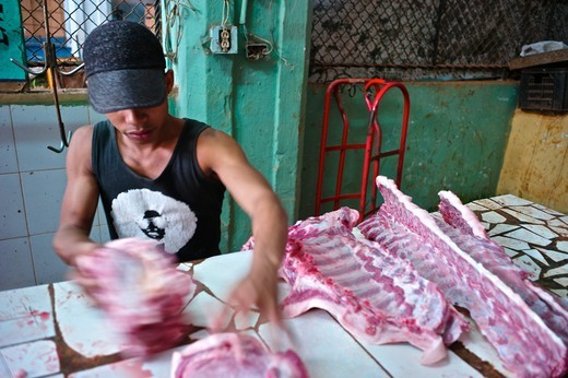 Cuba, Havana, Old Havana, Cuban selling meat ribs at indoor market : Stock Photo