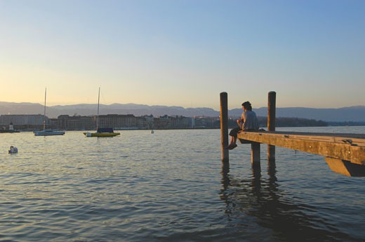 Couple in love sitting on the dock of the lake port  Geneva  Switzerland : Stock Photo