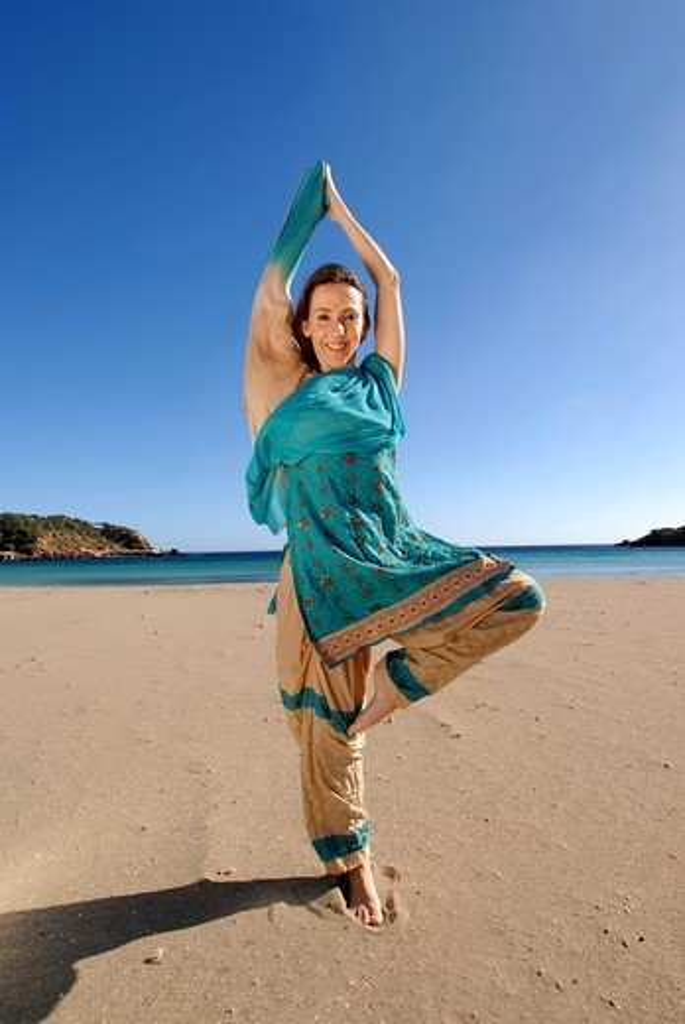 Stock Photo: 1938-3139 Yoga teacher and artist Lena Tancredi doing Tree Pose on the beach, Ibiza Island, Balearic Islands, Spain
