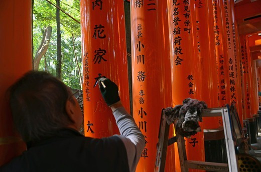 Stock Photo: 1938-3358 Restorer painting letters of a Torii gate at Fushimi Inari-Taisha shrine, Kyoto City, Honshu, Japan
