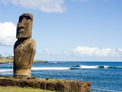 Stock Photo: 1940-1032 A moai ancestral spirit figure protectively watches over Rapa Nuians at a fishing harbor on Easter Island  Chile