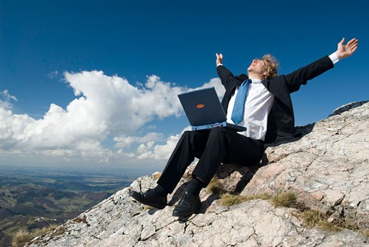 Stock Photo: 1947-1291 Young business man working with his laptop on a mountain