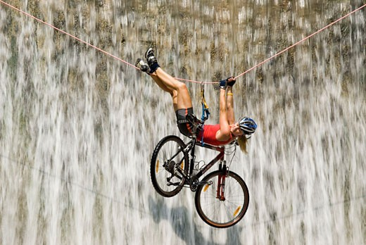 Crossing the waterfall with the bike : Stock Photo