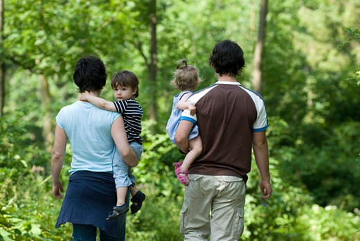 Austrian family taking a walk in the forest : Stock Photo