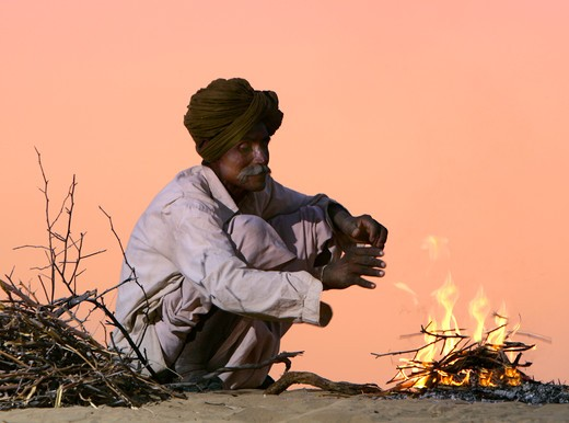 Tribesman Starting Wood Fire On Sand Dunes : Stock Photo