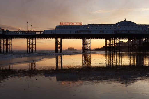 Sunset behind Brighton Pier with ruins of the West Pier in distance. : Stock Photo