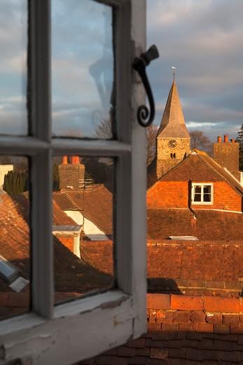 View through open window over rooftops of Burwash village. : Stock Photo