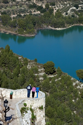 Spain - Valencia. Costa Blanca - Guadalest - Tourists peering over Guadales Castle walls with the reservoir below : Stock Photo