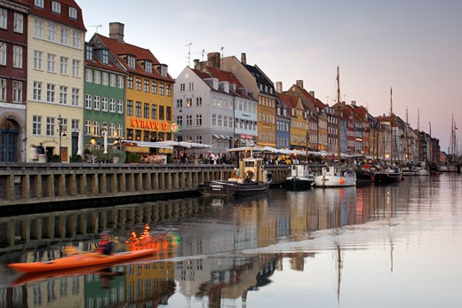 A Canoeist Paddles Past The Boats And Side-walk Cafes Along The Nyhavn Canal In Copenhagen : Stock Photo