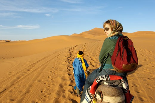 Berber Man In Traditional Outfit Leads  Woman On A Camel Through The Dunes Of Erg Chebbi, Periphery Of The Sahara Desert : Stock Photo