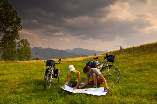Girl And Boy Cyclists At The Foot Of Fagaras Mountains Are Resting And Looking At Map, Transylvania, Romania : Stock Photo