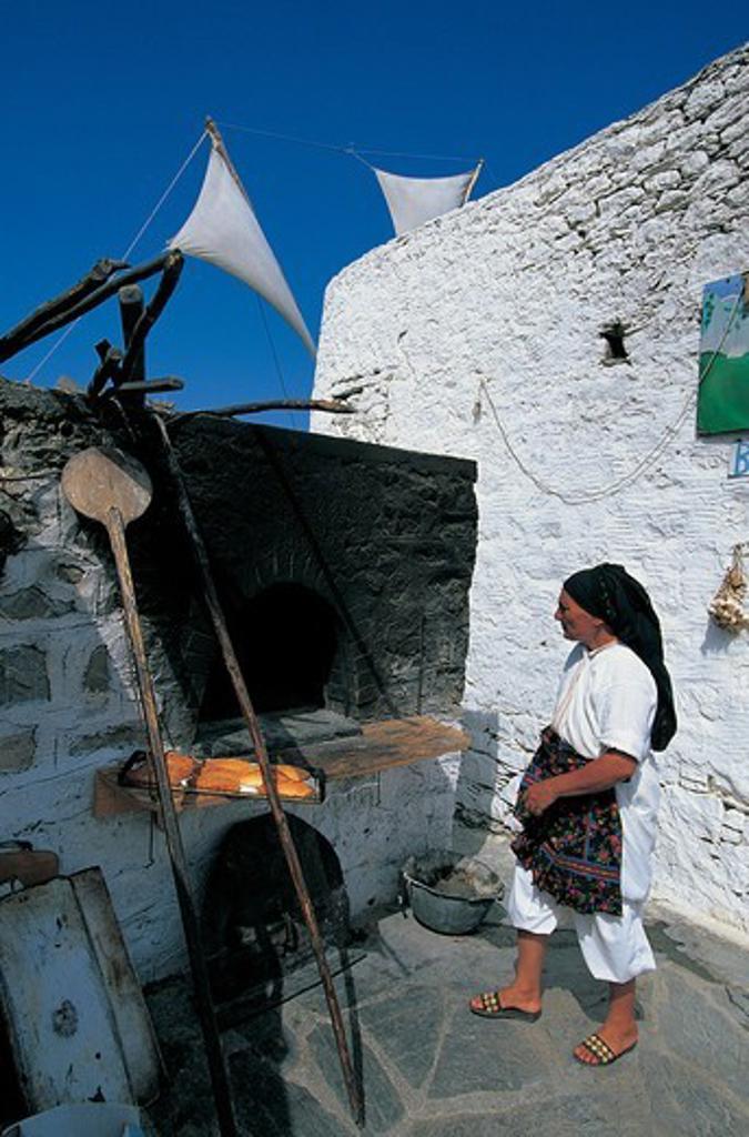 Greece, Dodecanese, Karpathos, Woman using stone oven : Stock Photo