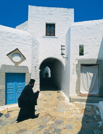 Greece, Dodecanese, Patmos Island, Priest walking through village : Stock Photo