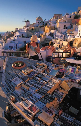 Greece, Cyclades, Santorini Island, Tourists reading books in Greek town : Stock Photo