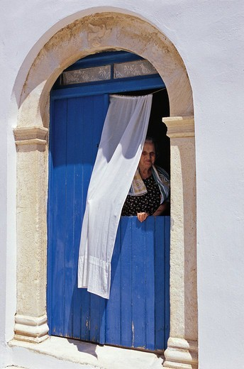 Stock Photo: 196-2580 Greece, Cyclades, Tinos island, Pyrgos village, Woman looking through door