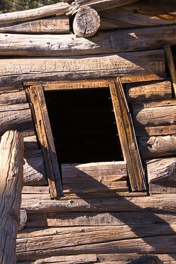 A closeup of a window in an old miners cabin near Virginia Lakes in the Sierra Mountains of California : Stock Photo