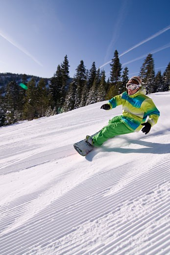 A man snowboarding on a freshly groomed slope on a sunny day at Northstar near Lake Tahoe in California : Stock Photo