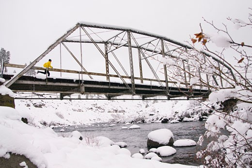 Stock Photo: 1989-1378 A man running across a trestle bridge on a snowy day near Truckee in California