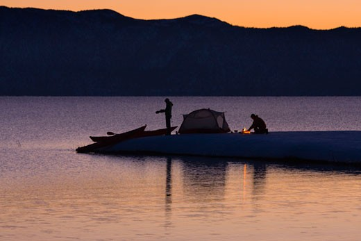 Stock Photo: 1989-1525 A man and a woman sea kayak camping on the shore of Lake Tahoe California in winter at sunrise